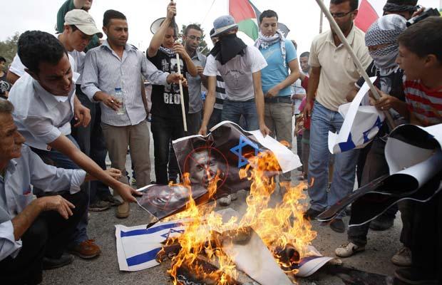 Palestinos queimam bandeiras de Israel e fotos de Obama durante protesto nesta sexta-feira (23) em Nabi Saleh, na Cisjordânia (Foto: AP)