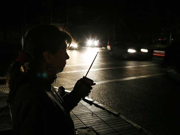 Uma mulher em Viña del mar, a cerca de 121 km de Santiago, escuta em um rádio as notícias sobre o apagão no país. (Foto: Eliseo Fernandez / Reuters)