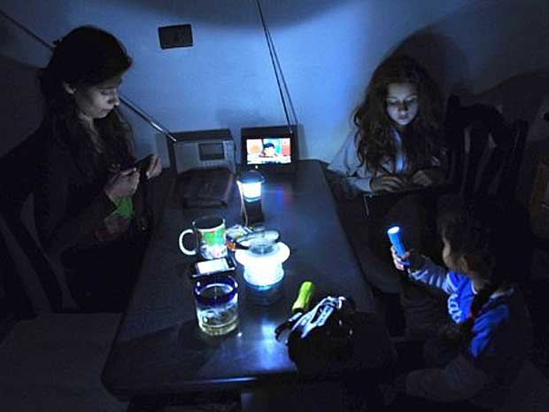 Uma família usa lanternas em uma mesa durante apagão em Santiago. (Foto: Martin Bernetti / AFP Photo)
