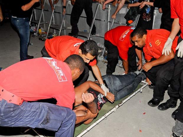 Seguranças socorrem fã retirado de multidão após passar mal (Foto: Flavio Moraes/G1)
