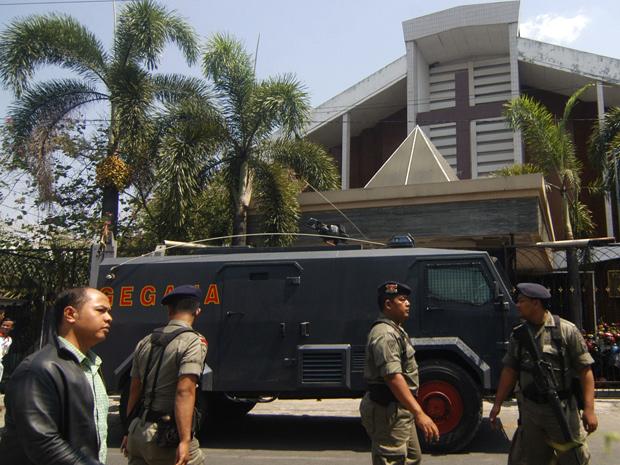Policiais vigiam a entrada da igreja Bethel Injil, em Surakarta, na Indonésia. (Foto: AP Photo)
