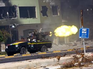 Integrantes das forças de transição na Líbia disparam contra tropas pró-Kadhafi neste domingo (25). (Foto: Amru Salahuddien / AP Photo / via BBC)