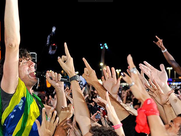 Gary Lightbody, do Snow Patrol, mergulha na primeira fila enrolado em uma bandeira do Brasil (Foto: Flavio Moraes/G1)