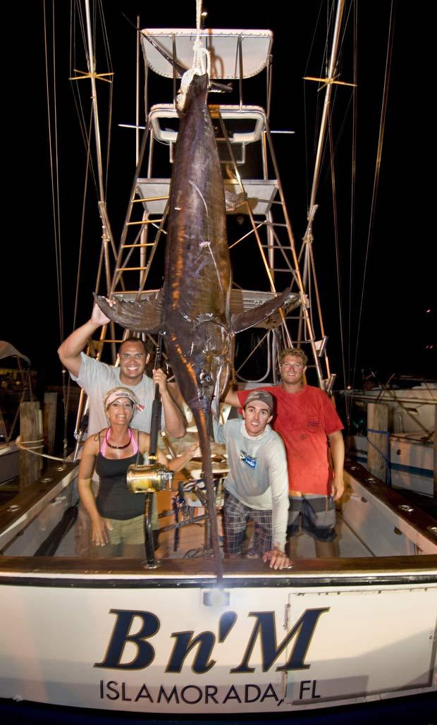 À esquerda, John White e sua mulher, Pamela, com o peixe-espada de 206 kg. À direita, o capitão Nick Stanczyk (esq) e Matt Davis. (Foto: Andy Newman/AP)