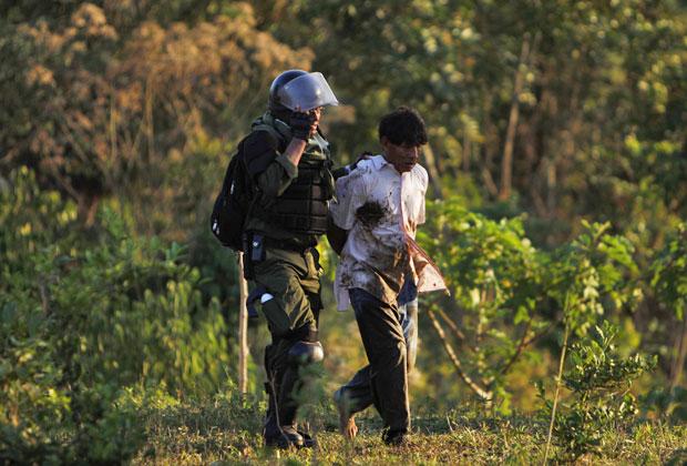 Policial prende homem já ferido pelos enfrentamentos na região de Yucumo, na Bolívia (Foto: Juan Karita/AP)