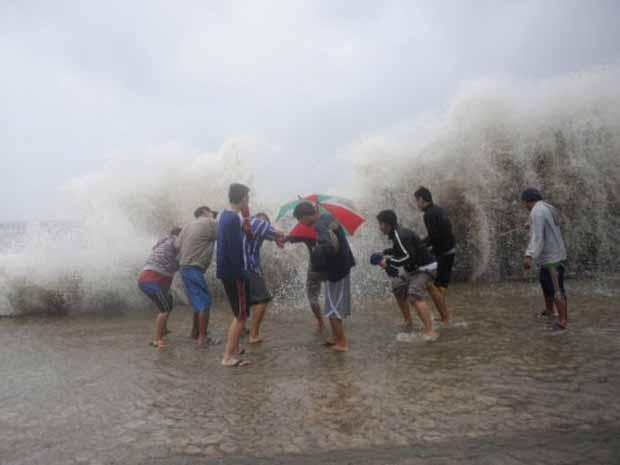 Moradores se divertem com as fortes ondas provocadas nesta terça-feira (27) pela passagem do tufão Nesat em Manila, capital das Filipinas (Foto: AFP)