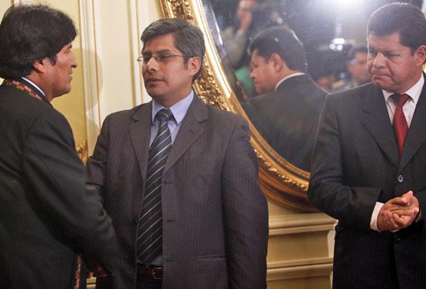 Evo Morales (esquerda) cumprimenta Wilfredo Chavez (centro) após ele ser empossado como novo ministro do Interior - ao lado de Ruben Saavedra  (Foto: Juan Karita/AP)