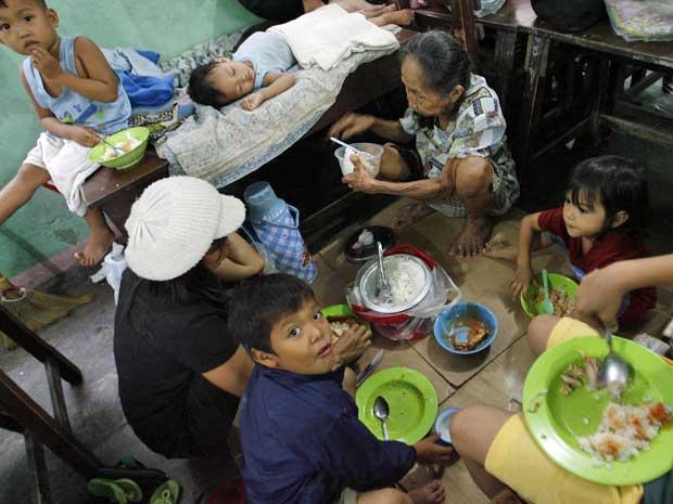 Família partilha refeição numa escola que foi transformada em abrigo. (Foto: Cheryl Ravelo / Reuters)