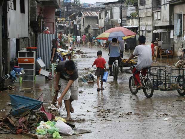 Moradores começam a voltar para suas casas e iniciam a limpeza do caos provocado pela passagem do tufão Nesat na cidade de Marikina. (Foto: Cheryl Ravelo / Reuters)