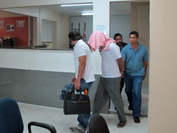 Com a cabeça encoberta por uma camisa, Felipe de Lorena é transferido de delegacia no início da noite desta sexta-feira (30)  (Foto: Marcelo Mora/G1)