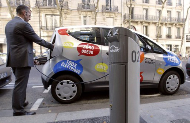Homem em ponto de abastecimento de carro elétrico em Paris (Foto: AFP)