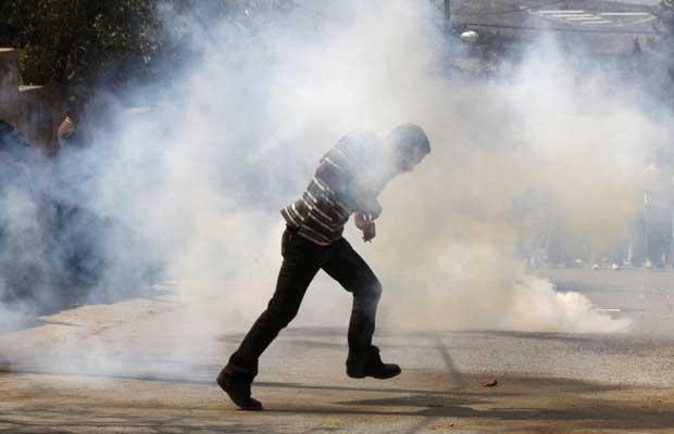 Manifestante palestino tenta escapar de bomba de gás lançada pela polícia israelense de fronteira durante protesto próximo a assentamento em Kofr Qadoum, na Cisjordânia, nesta sexta-feira (30) (Foto: Reuters)