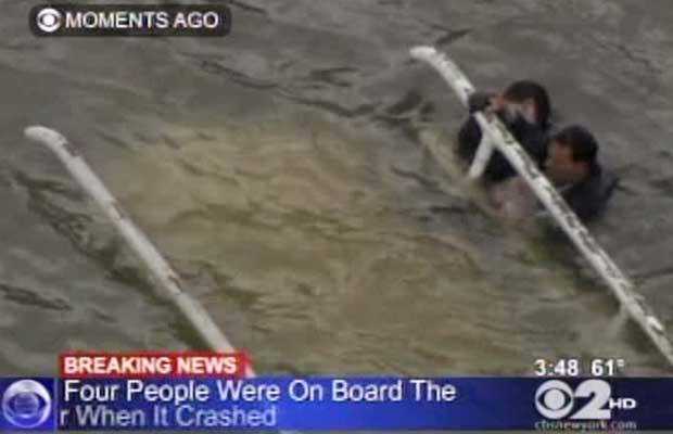 Imagem da TV WCBS mostra sobreviventes da queda do helicóptero agarrados à aeronave, submersa no East River, na tarde desta terça-feira (4) (Foto: AP)
