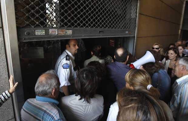 Funcionários públicos entram no prédio do Ministério de Finanças da Grécia nesta terça-feira (4) (Foto: AP)