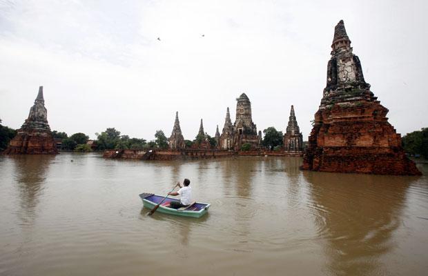 Barco atravessa região de Wat Chaiwatthanaram, patrimônio da Unesco alagado na Tailândia (Foto: Chaiwat Subprasom/Reuters)