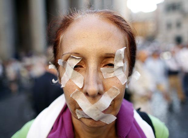 Mulher colocou fita adesiva nos olhos e na boca durante protesto em Roma nesta quarta (5) (Foto: Tony Gentile/Reuters)
