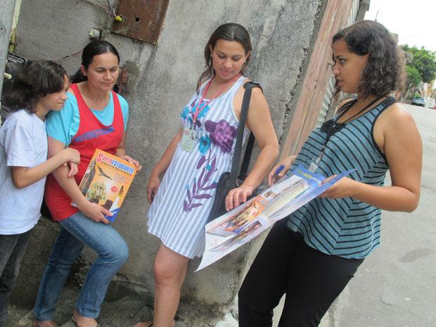 Vendedoras apresentam livros à moradora na Zona Sul de São Paulo (Foto: Darlan Alvarenga/G1)
