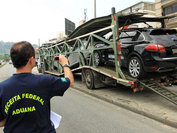 Agente da Receita Federal fotografa carros importados apreendidos em operação da Polícia Federal na Barra da Tijuca, Zona Oeste do Rio (Foto: Gabriel de Paiva/Agência O Globo)