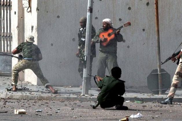 Soldado toca violão em meio a uma troca de tiros em Sirte nesta segunda (10) (Foto: Aris Messinis/AFP)