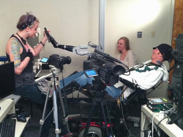 Tim interage com assistente no estudo que testou a eficiência do controle da mão artificial. (Foto: Keith Srakocic / AP Photo)