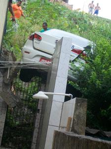 Táxi fica em cima do muro de uma casa ao descer ribanceira (Foto: Antônio Araújo/ Arquivo Pessoal)