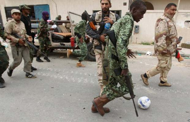 Combatente rebelde 'bate bola' após tomada de bairro da cidade líbia de Sirte nesta segunda-feira (10) (Foto: AFP)