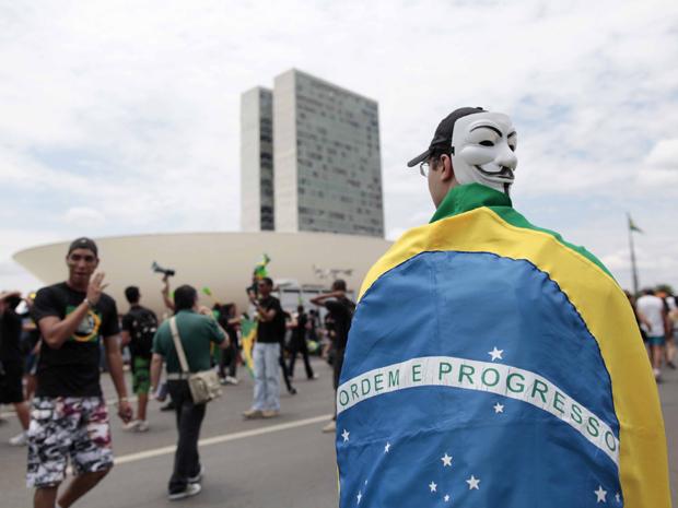 """Em Brasília, manifestantes usaram fantasias para protestar contra impunidade. Na foto, jovem caminha em direção ao Congresso como o personagem """"V"""". (Foto: Nelson Antoine/Fotoarena/AE)"""