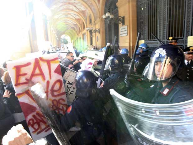 Manifestantes italianos enfrentaram policiais em frente ao Banco da Itália em Bolonha, nesta quarta-feira (12), em mais um dia de protestos contra a crise financeira. O governo italiano aprovou cortes de gastos de 45,5 bilhões de euros no orçamento até 2013 para equilibrar as conas do país. (Foto: Reuters)