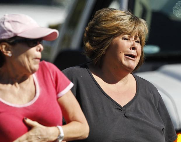 Testemunhas se desesperam ao ver a cena do crime em que seis pessoas foram mortas num salão de beleza da Califórnia (Foto: hris Carlson / AP)