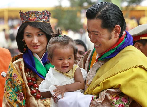 O rei segura criança ao receber felicitações pelas bodas (Foto: AP)