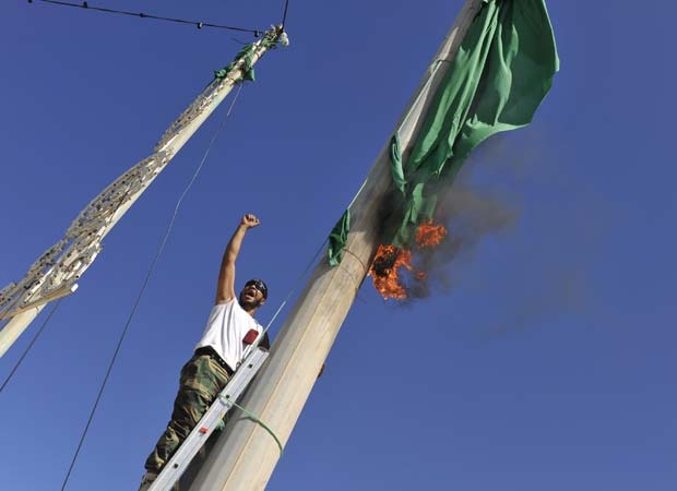 Combatentes do novo governo da Líbia queima bandeira do regime de Kadhafi nesta quarta-feira (12) em Sirte (Foto: AP)