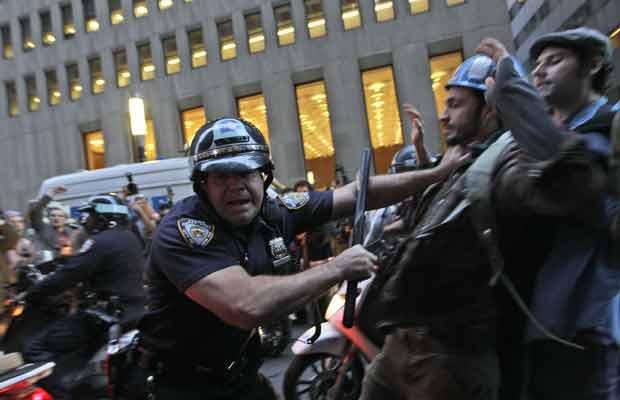 Manifestantes encaram policiais durante protesto próximo a Wall Street nesta sexta-feira (14) (Foto: AP)