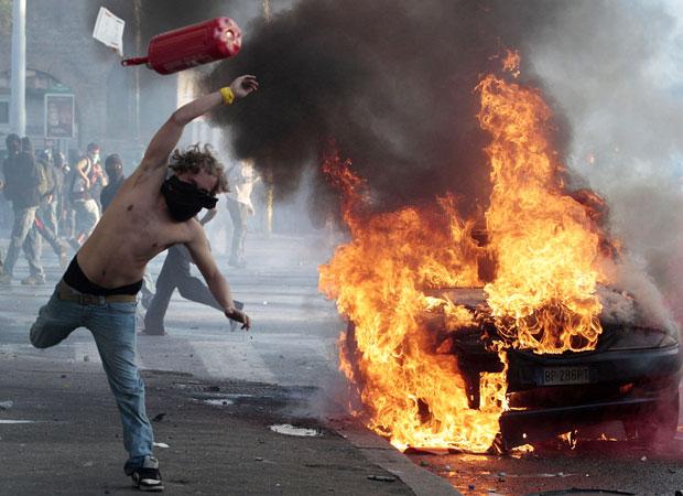 Jovem atira extintor durante protesto em Roma (Foto: AP)