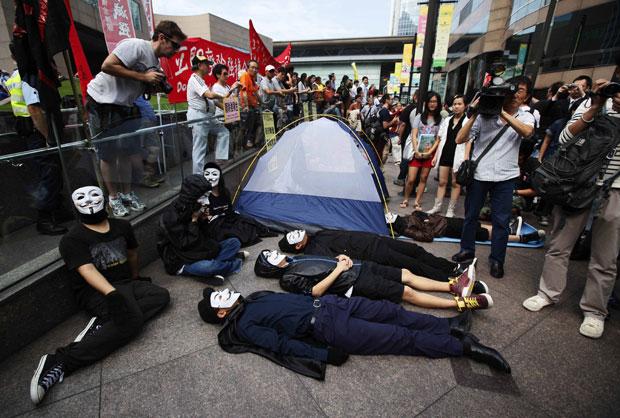 Manifestantes se deitam no chão em protesto em Hong Kong (Foto: Kin Cheung/AP)