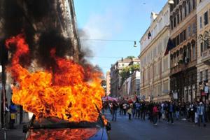 Manifestantes caminharam pelas ruas de Roma, na Itália, neste sábado. Um carro estacionado no caminho do protesto pegou fogo (15) (Foto: AFP)