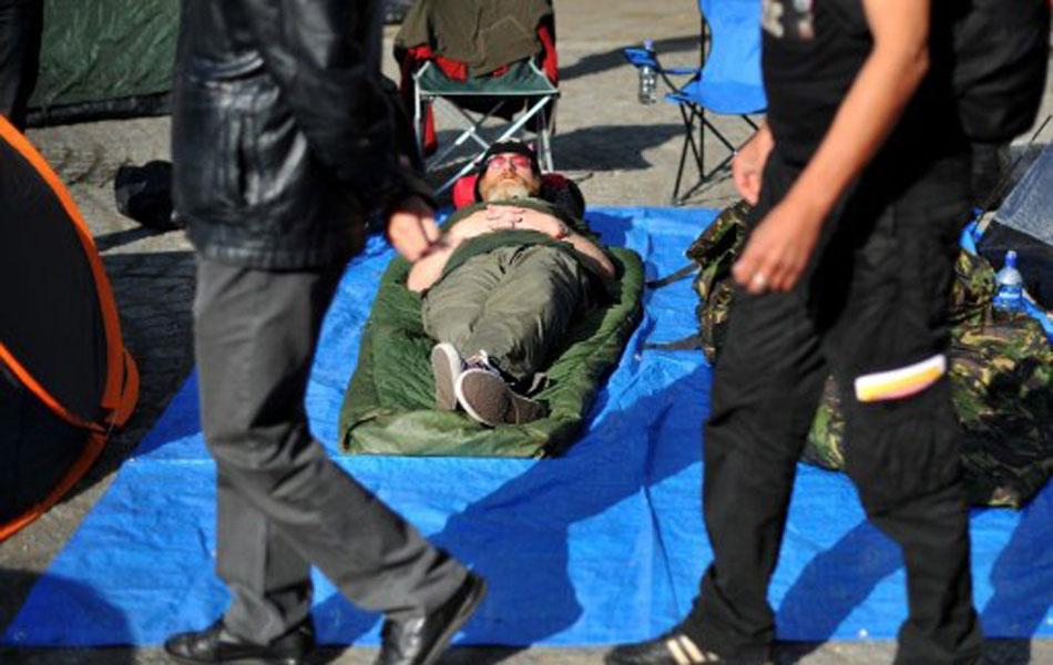 Homem dorme em acampamento improvisado pelos manifestantes em praça de Londres