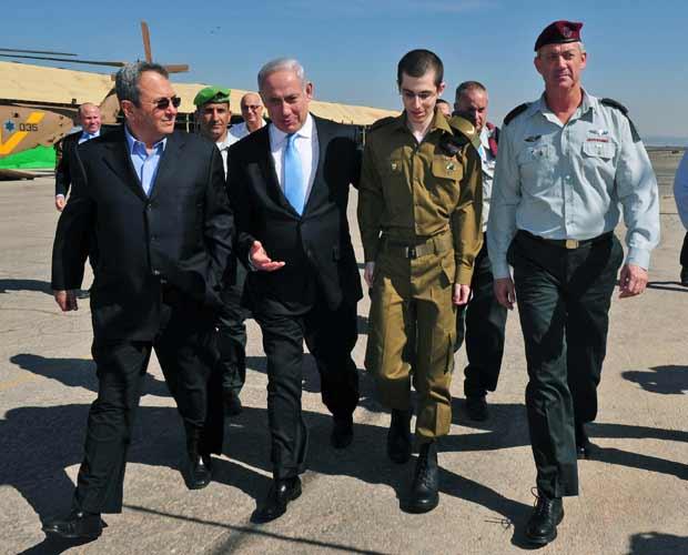 O soldado Gilad Shalit caminha ao lado do premiê de Israel, Benjamin Netanyahu, (no centro, à esquerda), do ministro da Defesa, Ehud Barak (esquerda) e do chefe de gabinete Benny Gabtz, em Tel Aviv, nesta terça-feira (18) (Foto: AP)