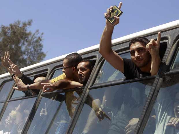 Palestinos libertados acenam de ônibus ao chegar à Faixa de Gaza, pela passagem de Rafah, nesta terça-feira (18) (Foto: Reuters)