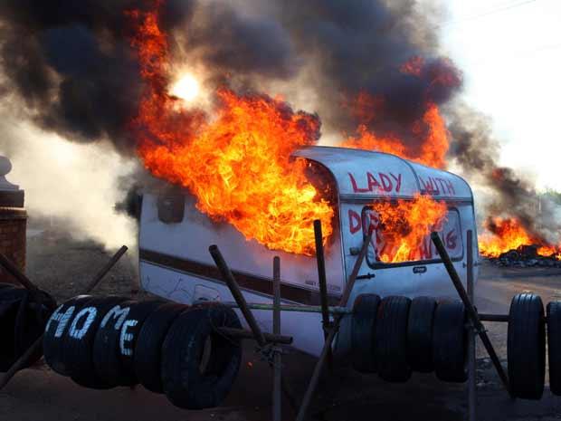 Trailer queimado durante o confronto desta quarta-feira (19) no acampamento cigano (Foto: AP)
