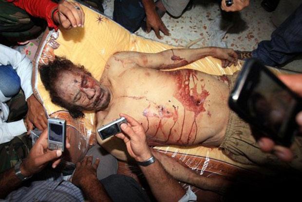 Soldados da transição fotografam o corpo de Muammar Kadhafi (Foto: AFP)