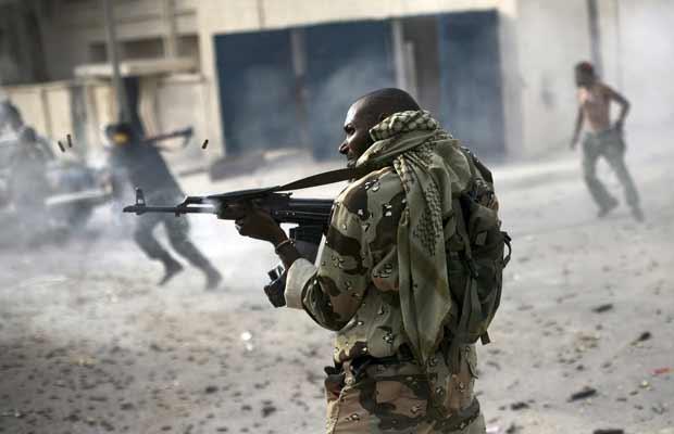 Combatente leal aos ex-rebeldes da Líbia atira contra kadhafistas em combate nesta quarta-feira (19) em Sirte (Foto: AP)