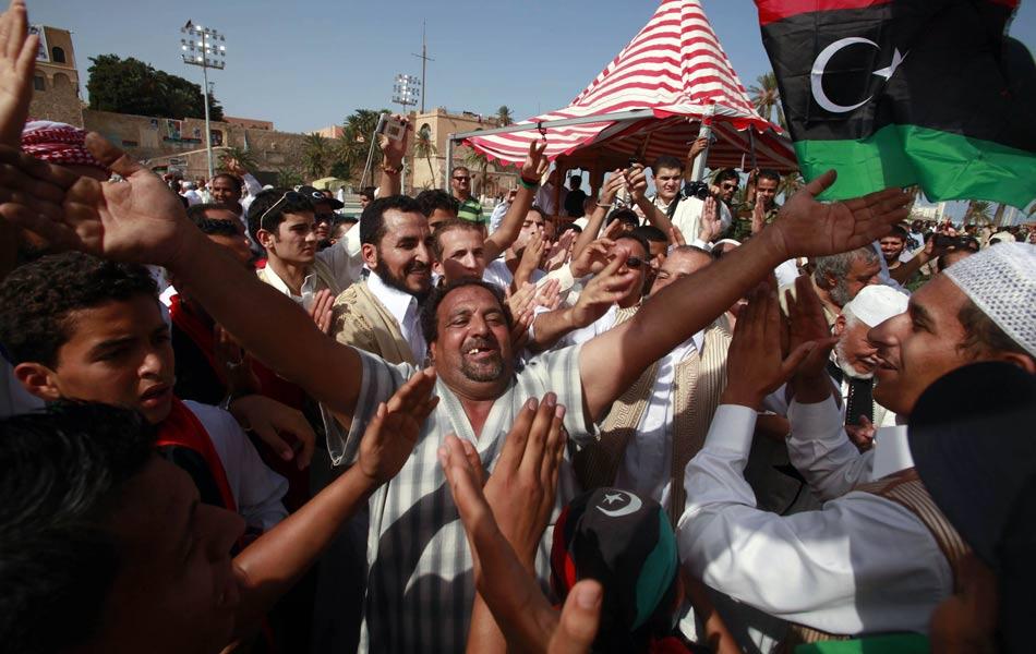 Líbios comemoram nesta sexta-feira (21) na Praça dos Mártires, em Trípoli, a morte do ex-ditador Muammar Kadhafi.