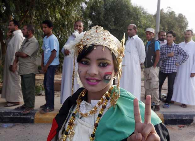 Garota faz sinal da vitória nesta sexta-feira (21) em fila para ver o corpo do ex-ditador da Líbia, Muammar Kadhafi, em Misrata (Foto: AP)