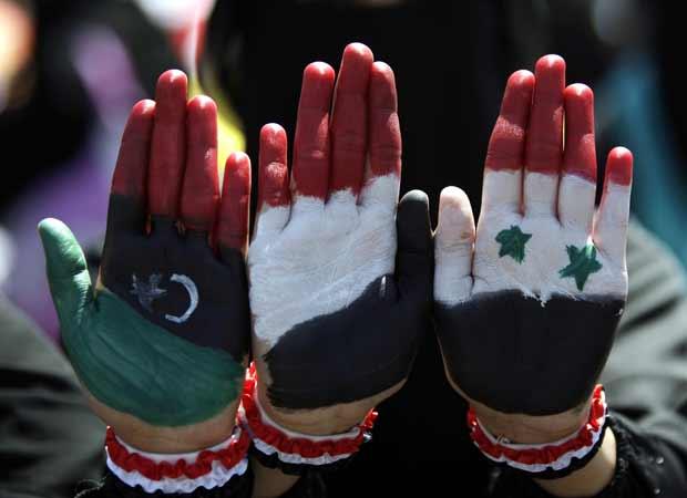 Mulheres mostram bandeiras de Líbia, Iêmen e Síria nesta sexta-feira (21) em ato contra o governo iemenita na capital, Sanaaria (Foto: AP)