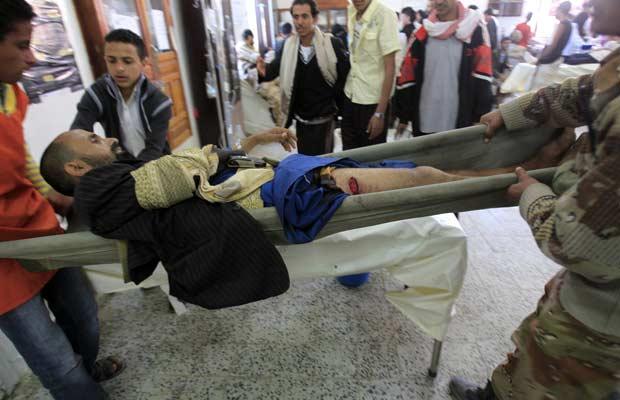 Combatente tribal ferido é carregado em maca durante confrontos em Sanaa neste sábado (22) (Foto: AFP)