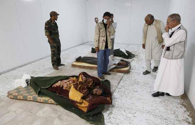 Moradores observam os corpos de Kadhafi, Muatassim e do chefe militar do antigo regime, nesta segunda-feira (24), em Misrata (Foto: AP)