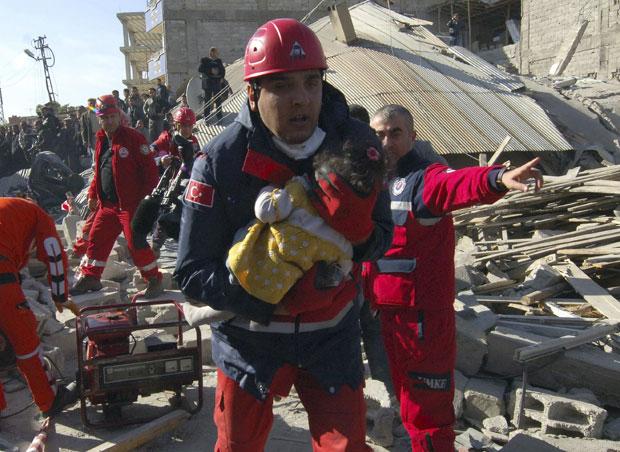 Oficial de resgate retira uma menina encontrada em meio aos escombros ainda com vida nesta segunda (24) em Ercis, perto da cidade de Van (Foto: Reuters)