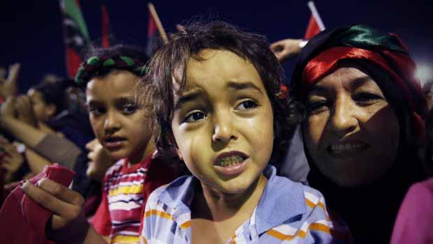 Líbios celebram a libertação do país, neste domingo (23), em praça na capital, Trípoli (Foto: AP)
