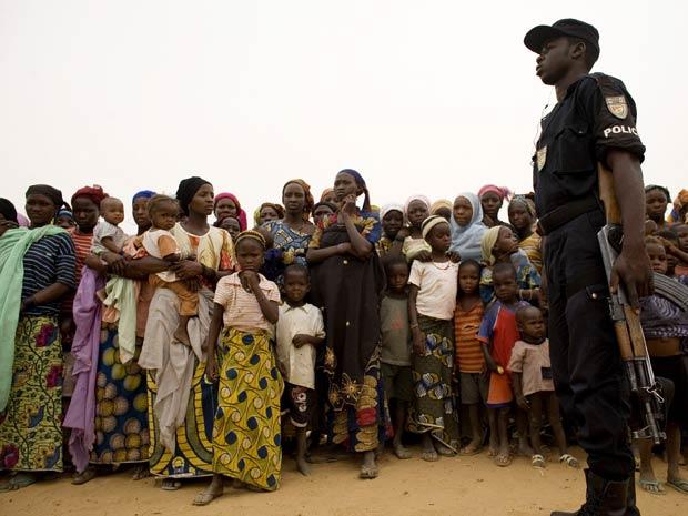 Policial controla presença famílias do Níger que passam fome após o governo pedir ajuda para lidar com escassez de alimentos (Foto: The New York Times)