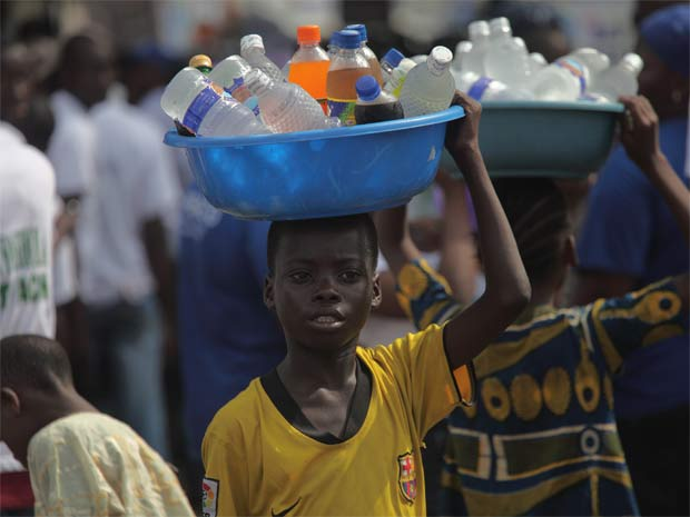 Garoto nigeriano vende garrafas de água em Lagos (Foto: Akintunde Akinleye/UNFPA)